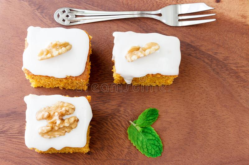 Pieces of homemade carrot cake with icing cream on white plate. royalty free stock image