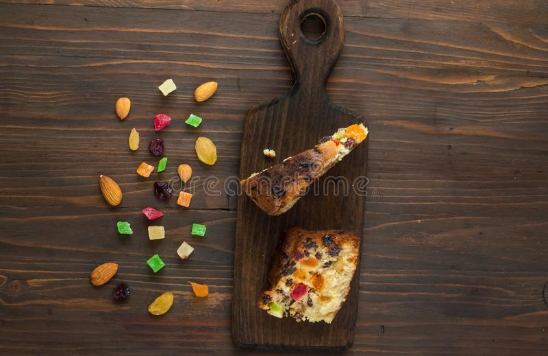 Pieces of homemade muffins with raisins, candied fruits and almonds on a wooden background, top view, copy space, close up stock photo