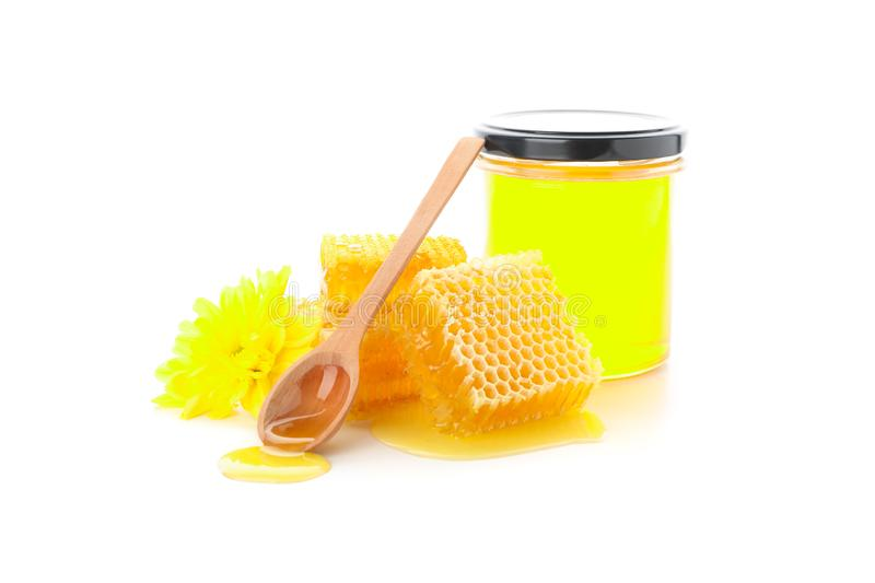 Pieces of honeycomb, glass jar, spoon and chrysanthemum isolated. On white background stock image