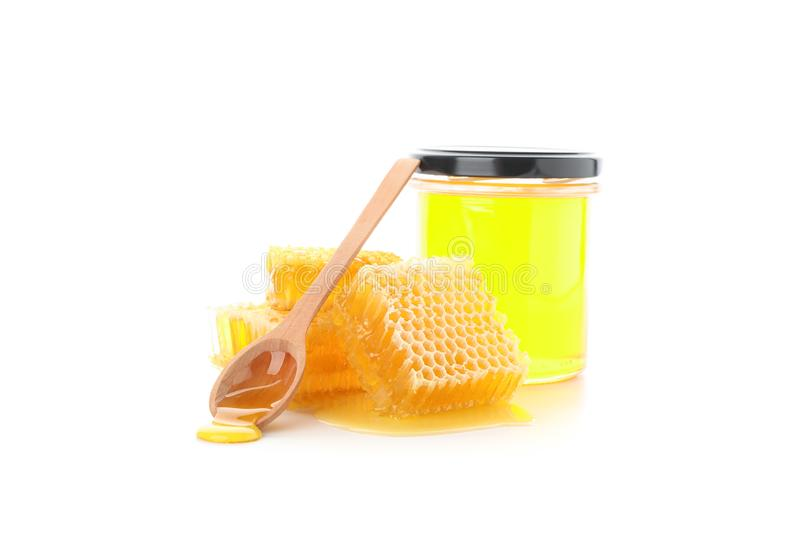 Pieces of honeycomb, glass jar and spoon isolated. On white background stock photo
