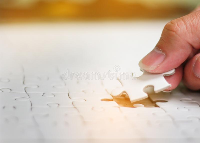 Jigsaw puzzle. Pieces of jigsaw on hand with light glow, Woman is trying to connect puzzle piece,Soft focus royalty free stock photography