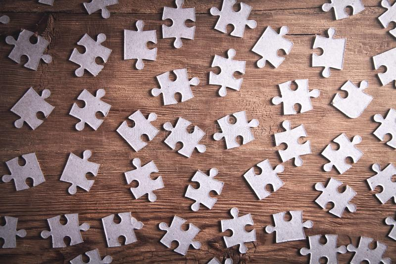 Pieces of the jigsaw puzzles on wooden background stock images