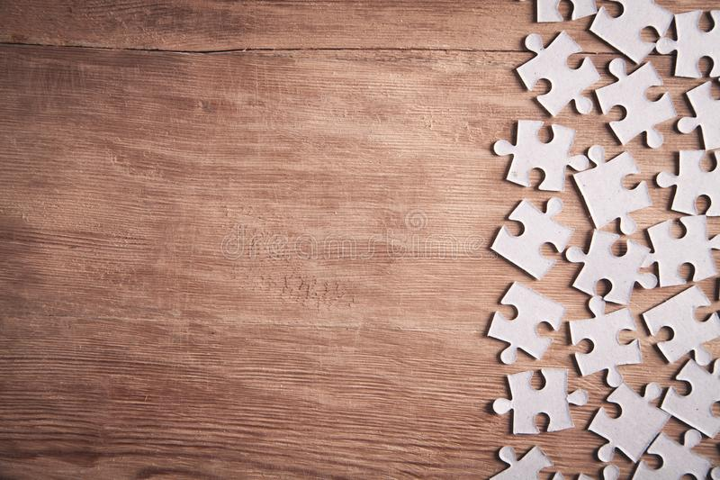 Pieces of the jigsaw puzzles on wooden background stock photo