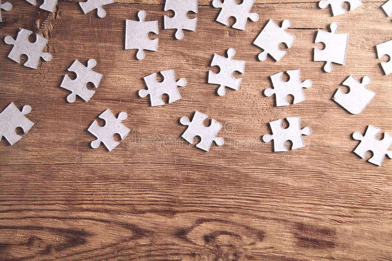 Pieces of the jigsaw puzzles on wooden background royalty free stock images