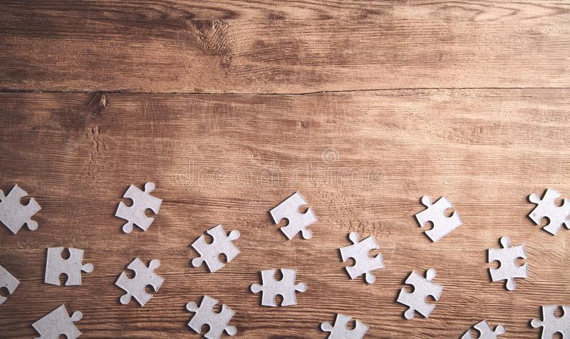 Pieces of the jigsaw puzzles on wooden background royalty free stock photo