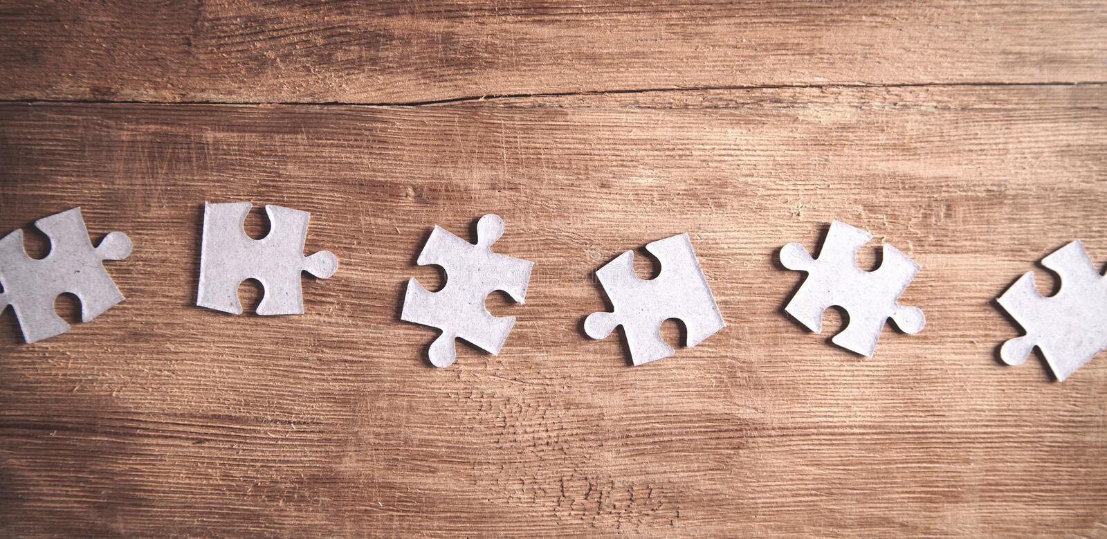 Pieces of the jigsaw puzzles on wooden background stock photos