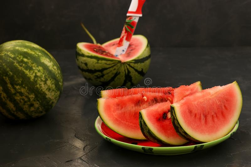 Pieces of juicy watermelon are located on a plate on a dark background stock images