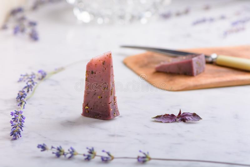 Pieces of lavender cheese and lavender flowers on a white marble worktop stock photo