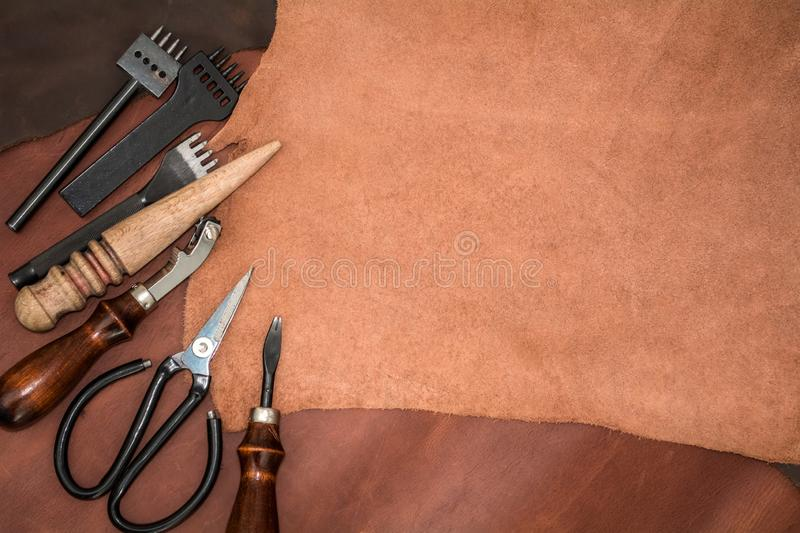 Pieces of leather and working tools. Craftman`s workspace.  royalty free stock image