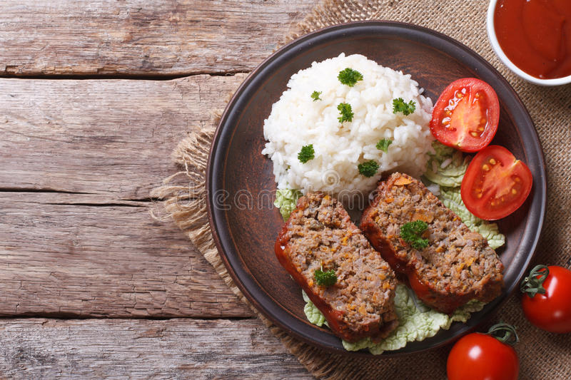 Pieces of meat loaf and rice, vegetables on a plate top view stock image