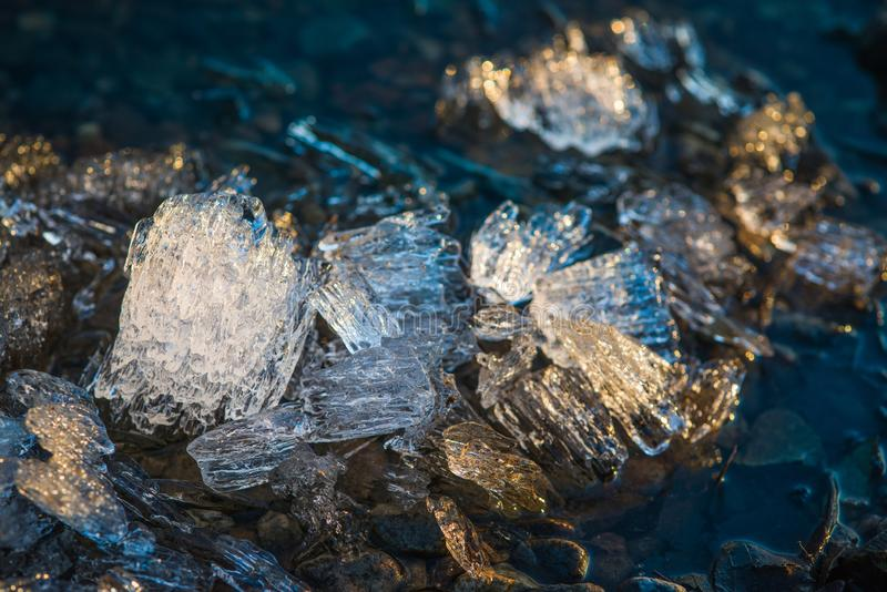 Pieces of melting ice under the bright Spring sun on the river bank. Selective focus macro shot with shallow DOF.  royalty free stock images