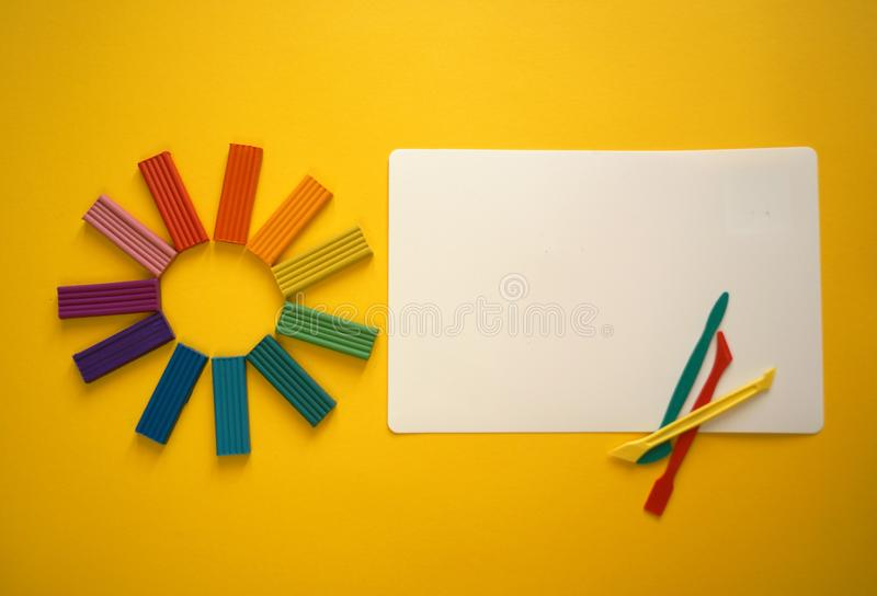 Pieces of multicolored plasticine for children against a yellow background. stock photo