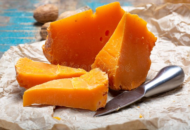 Pieces of native French aged cheese Mimolette, produced in Lille. With greyish curst made by special cheese mites close up stock images