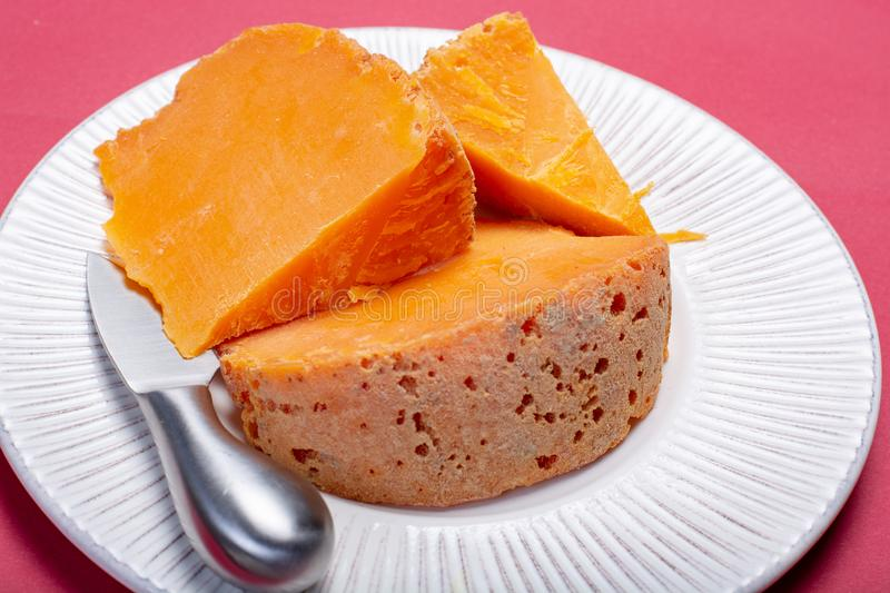 Pieces of native French aged cheese Mimolette, produced in Lille. With greyish curst made by special cheese mites close up royalty free stock image