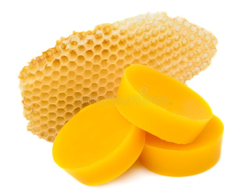 Pieces of natural beeswax and a piece of honey cell are isolated on a white background. Beekeeping products. Apitherapy. stock photo