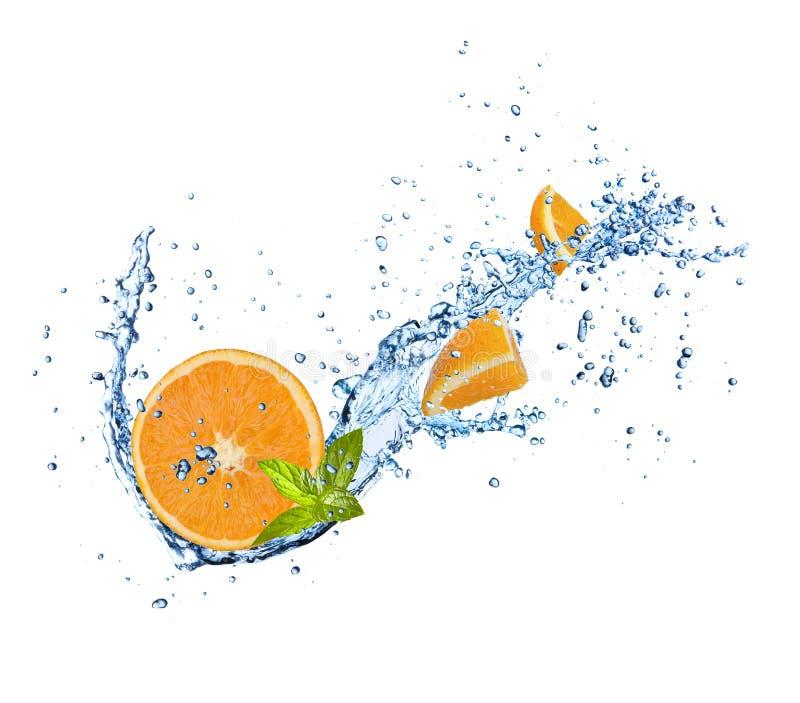 Pieces of orange in water splash on white stock photos