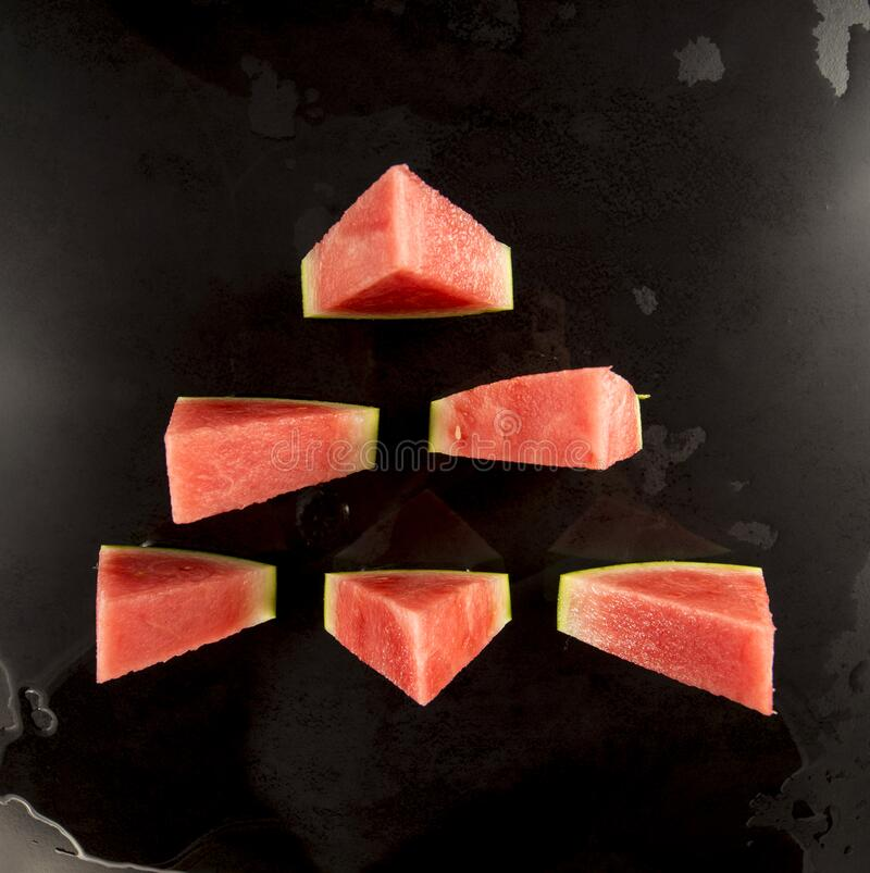 Pieces of watermelon in a black tray on a black background. Pieces of organic watermelon in a black tray on a black background stock images
