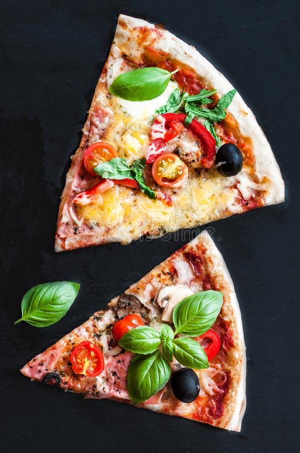 Pieces of Pizza Margarita with tomatoes, basil, champignon mushrooms and cheese. Margherita Pizza on black stone background stock photography