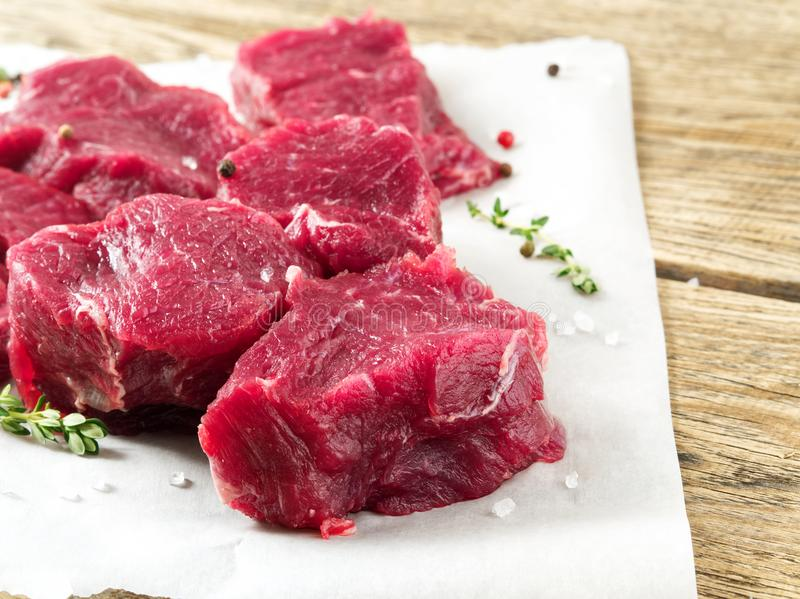 Pieces of raw meat. Raw beef with spices on white parchment paper on wooden rough rustic background, side view, close-up royalty free stock photography