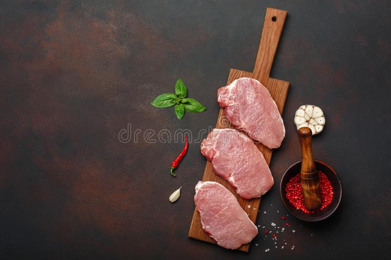 Pieces of raw pork steak with basil, garlic, pepper, salt and spice mortar on cutting board and rusty brown background with space royalty free stock photos