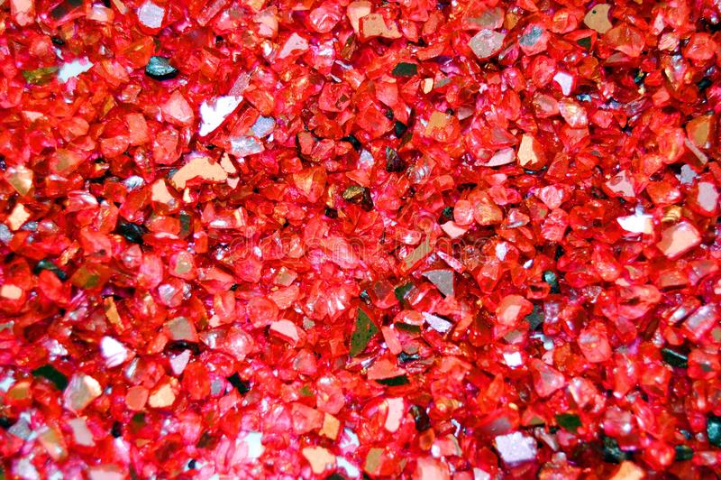 Texture of broken glass pieces, payment red glitter background. Holidays, Christmas, Valentine, love abstract texture. Pieces of red broken glass suitable for stock photos