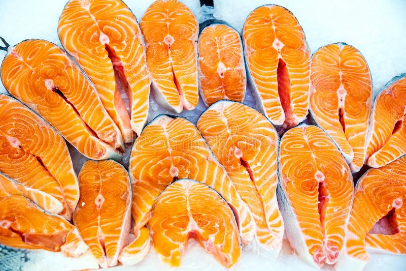 Fresh fish at the store counter. Pieces of red fish lie on ice for storage in a store stock photography