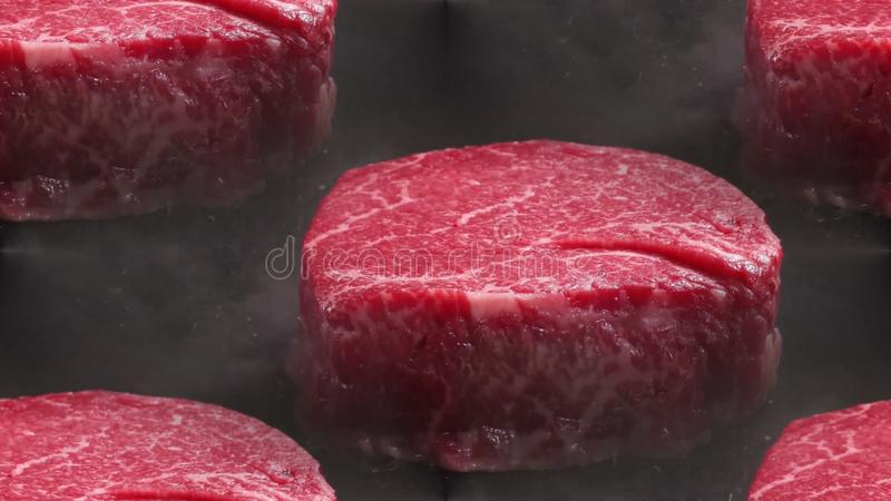 Pieces of red meat. Round pieces of red meat is fried on a griddle royalty free stock photography