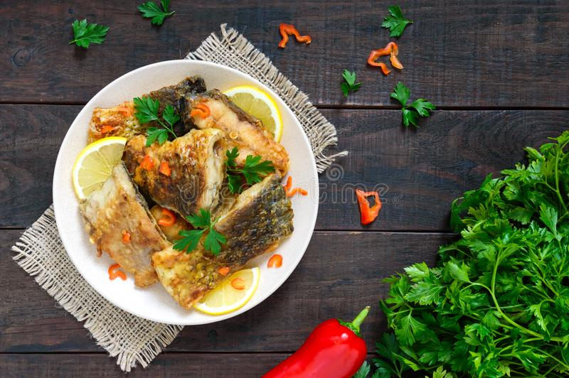 Pieces of roasted carp with lemon and greens on a plate on a dark wooden background royalty free stock image