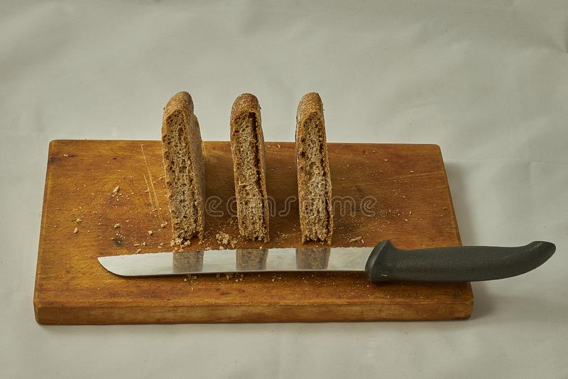 Pieces of rye bread cut on a wooden board next to a bread-cutting knife. stock images