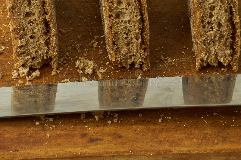 Pieces of rye bread cut on a wooden board next to a bread-cutting knife. The metal knife has the reflections of the bread on it stock image