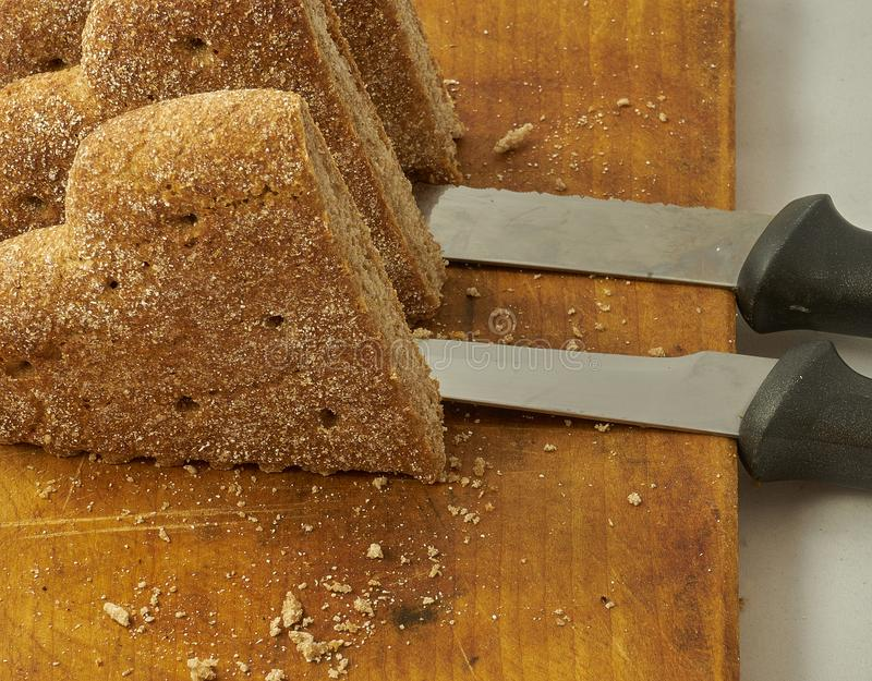 Pieces of rye bread cut on a wooden board next to a two bread-cutting knifes. Above the wood cutting board are a few breadcrumbs royalty free stock image