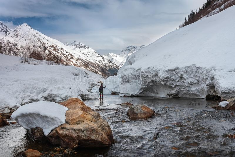 Pieces of snow from the mountain avalanche in the river against the backdrop of mountain peaks. The Gonachkhir river Karachay-Cherkess Rep. Russia stock photography