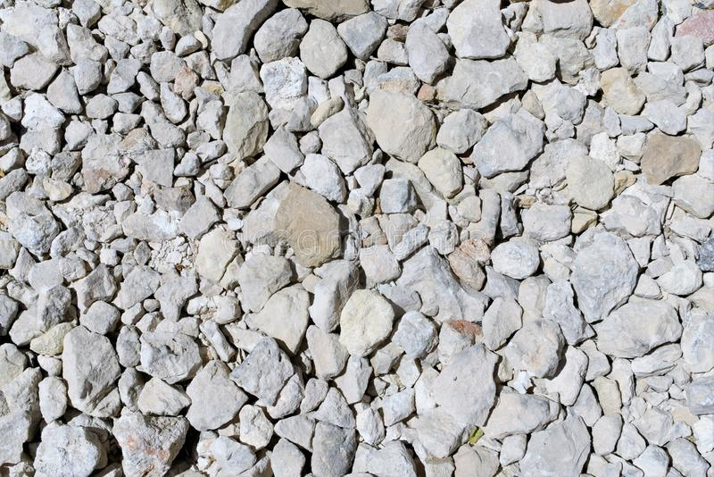 Original background from fragments of Maltese stone. Pieces of stone of different sizes with sharp edges make up an interesting pattern, unpredictable and stock photos
