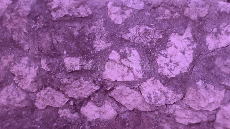 Pieces of stones. Purple rough old stone wall in horizontal shape stock photo
