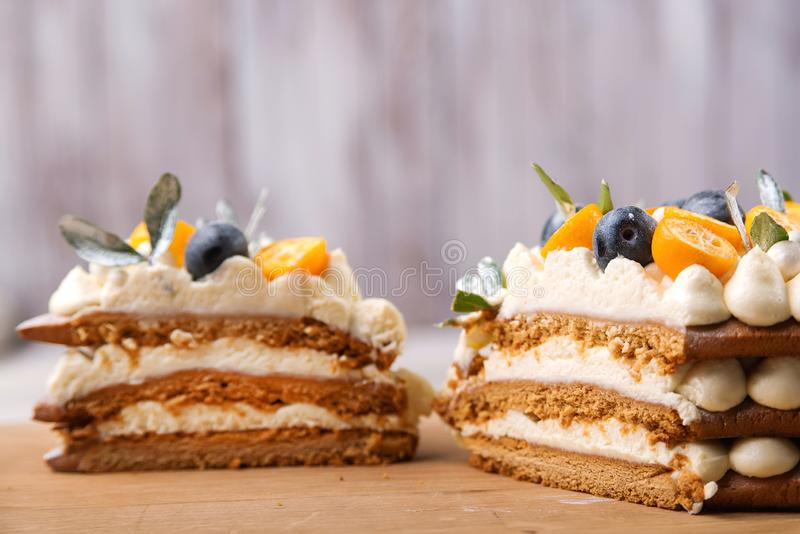 Pieces of sweet homemade layered honey cake decorated with kumquat and berry. Fruit cake over wooden background. Christmas royalty free stock image