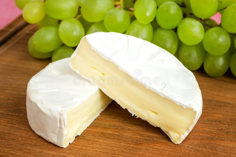 Pieces of tasty cheese camembert and sweet green grapes on a brown wooden cutting board. Soft cheese with edible white mold. Pieces of tasty cheese camembert and royalty free stock photo
