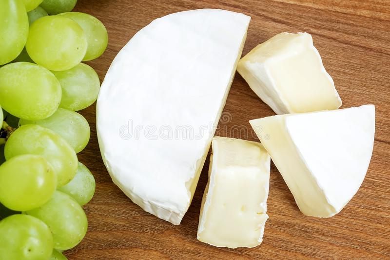 Pieces of tasty cheese camembert and sweet green grapes on a brown wooden cutting board. Soft cheese with edible white mold. Pieces of tasty cheese camembert and royalty free stock images