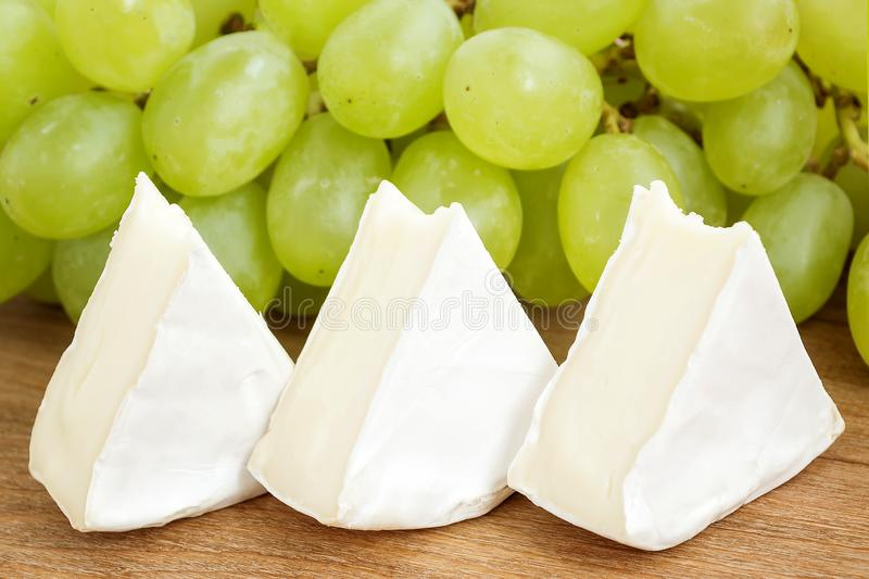 Pieces of tasty cheese camembert and sweet green grapes on a brown woodwn cutting board. Soft cheese with edible white mold. Pieces of tasty cheese camembert and stock images