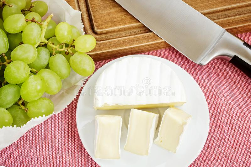 Pieces of tasty cheese camembert on white plate and sweet green grapes on a pink tablecloth. Soft cheese with edible white mold. Pieces of tasty cheese camembert stock photo