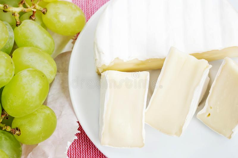 Pieces of tasty cheese camembert on white plate and sweet green grapes on a pink tablecloth. Soft cheese with edible white mold. Pieces of tasty cheese camembert royalty free stock photo