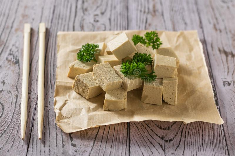 Pieces of tofu with greens on paper and chopsticks. Soy cheese. stock photography