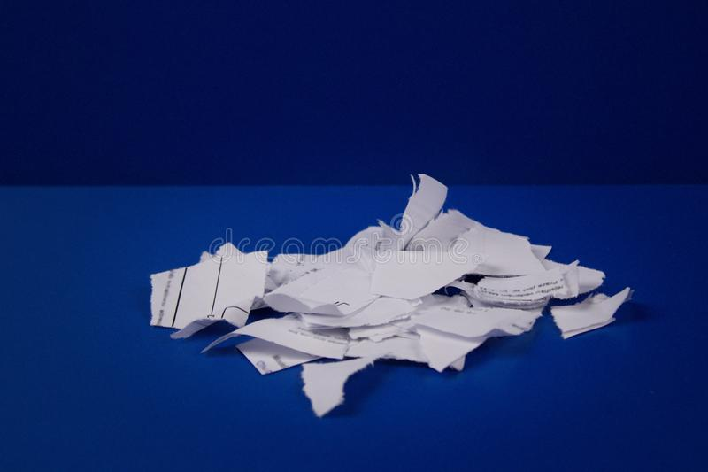 Pieces of torn paper with text on a blue background. stock photos