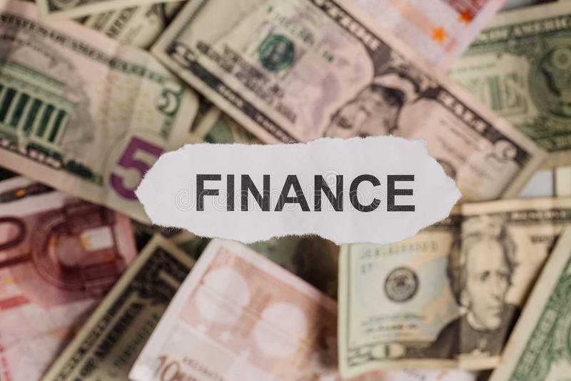 Pieces of torn white paper with FINANCE word on money blur background. royalty free stock photos