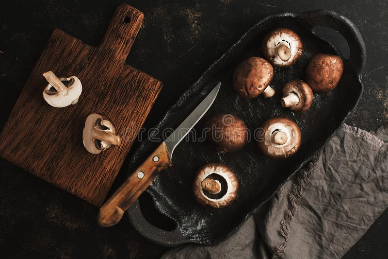 Pieczarki na handmade ceramicznym artykuły Wciąż życie kneblujący brzmienie Pieczarka ciie w połówki na tnącej desce Odgórny wido zdjęcie stock