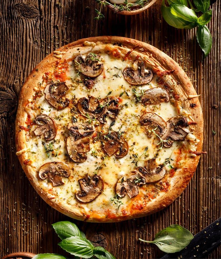 Pieczarkowa pizza z dodatek mozzarelli ziele na drewnianym stole i serem zdjęcia stock