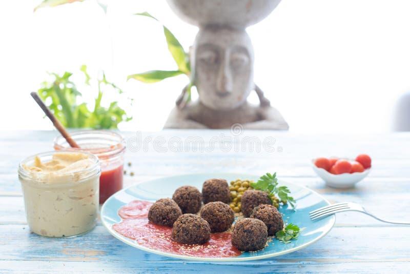 Pieczarkowi weganinów klopsiki z hummus i smażącym pomidorem, Albà ³ Ndigas Veganas De champiñones przeciwu hummus y tomate frit obraz stock