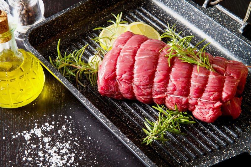 Pieczeń wołowina z rozmarynami na półkowym garnku na czerni obraz stock