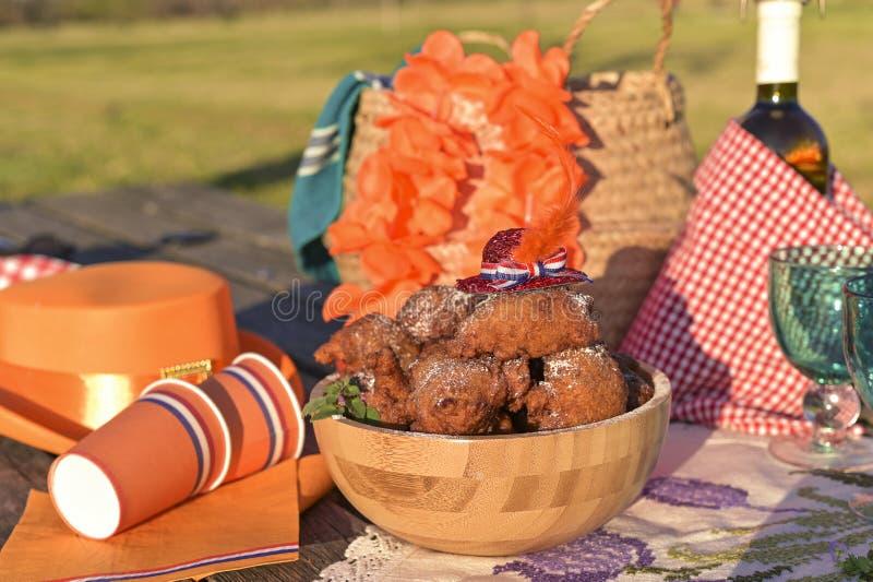 Pieczenie i różne potrawy i napoje na obiad o naturze Kapelusz i akcesoria Oranjevaya Tradycyjne pączki na Dzień Króla fotografia stock
