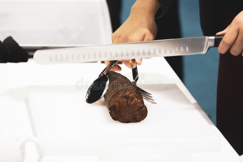 Pieczona wołowina i plasterek, szef kuchni ręki ciie pieczoną wołowinę, Rzeźbi pieczoną wołowinę obrazy stock