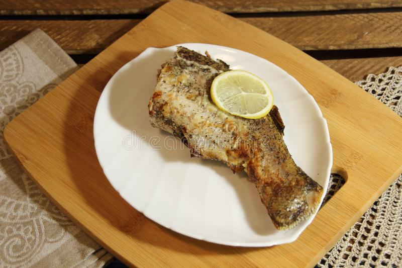 Pieczone nadziewane ryby luce ogon z cytryną na białym talerzu na drewnianym tle obraz royalty free
